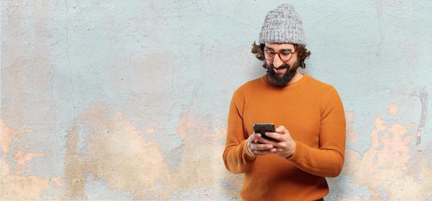 Joven barbudo con un teléfono inteligente