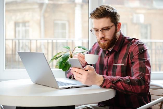 Joven barbudo tomando café mientras usa la computadora portátil y el teléfono.
