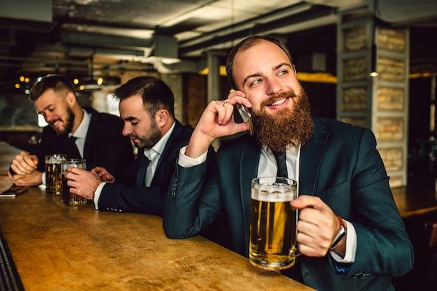 Joven barbudo en traje de hablar por teléfono. se sienta en la barra del bar y sostiene la jarra de cerveza. guy sonrie. otros dos hombres se sientan detrás.
