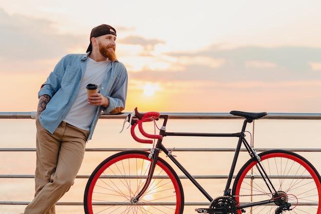 Joven barbudo viajando en bicicleta al mar al atardecer