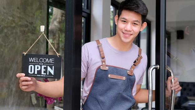 El joven barista asiático abre una puerta de vidrio para recibir a los clientes.