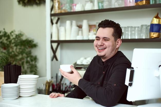 Joven barista caucásico sostiene una taza de café y sonríe detrás de la barra