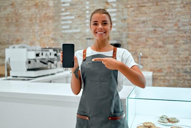 Joven barista se encuentra en el mostrador de una cafetería y sonríe mientras muestra la pantalla de un teléfono inteligente en blanco.