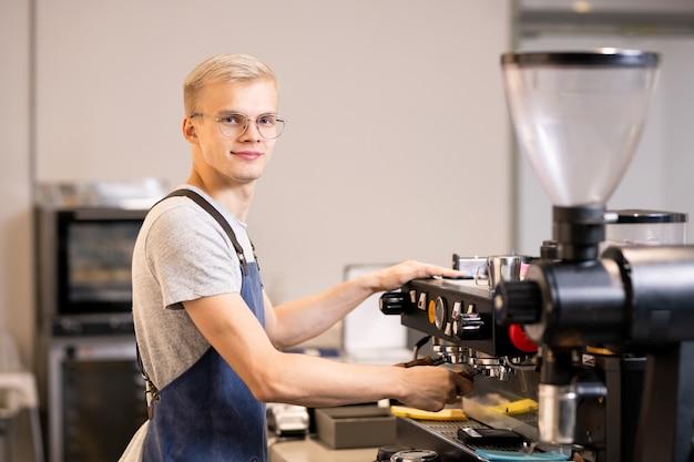 Joven barista exitoso en uniforme con máquina de café mientras está de pie