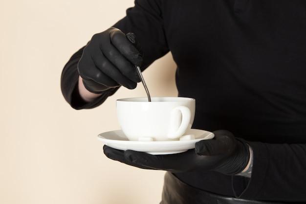 Joven barista en traje de trabajo negro con ingredientes y equipo de café semillas de café marrón con máscara estéril negra sobre blanco