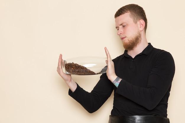 Joven barista en traje de trabajo negro con ingredientes y equipo de café semillas de café marrón sobre blanco
