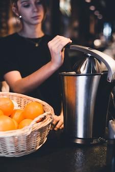 Joven barman juicing naranjas en el restaurante