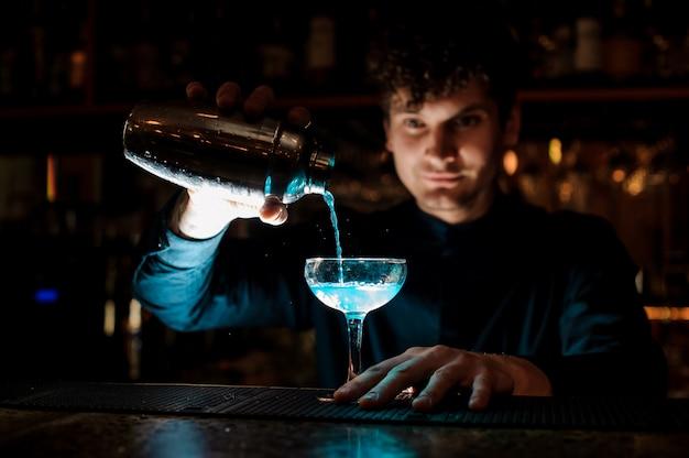 Joven barman sonriente vertiendo bebida fresca con licor azul de una coctelera en un vaso con colador