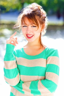 Joven bastante alegre adolescente asiática posando en el parque de la ciudad en un agradable día de verano, tiene un estado de ánimo positivo y juguetón, sonriendo y divirtiéndose, vistiendo un suéter a rayas casual. retrato de estilo de vida brillante.