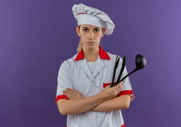 Joven bastante cocinero en uniforme de chef sosteniendo pinzas y cuchara mirando
