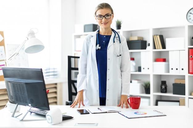 Una joven con una bata blanca está de pie cerca de una mesa en su oficina. un estetoscopio cuelga de su cuello.