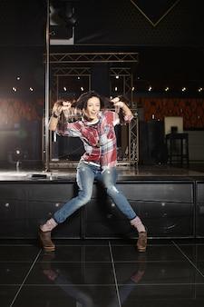 Joven beautifu divertido cantante de estrella del pop con micrófono sentado en la escena en el club.