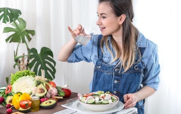 Una joven bebe agua en una mesa con verduras sobre un fondo claro, vestida con ropa de mezclilla. concepto de comida y bebida saludable.