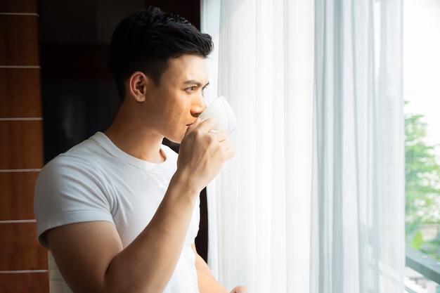 Joven bebe café en casa