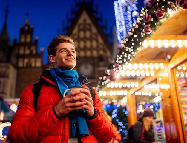 Joven con bebida en el mercado de navidad en wroclaw, polonia
