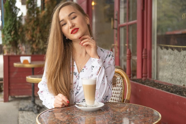 Joven bebiendo café en un café parisino de la calle