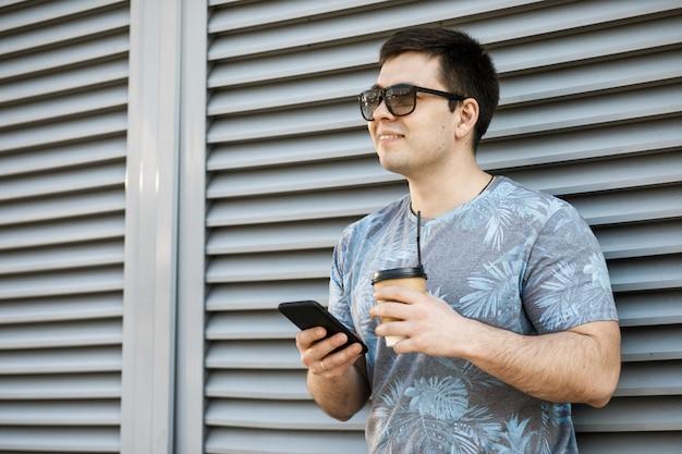 Joven bebiendo café en la ciudad y mirando a un teléfono móvil