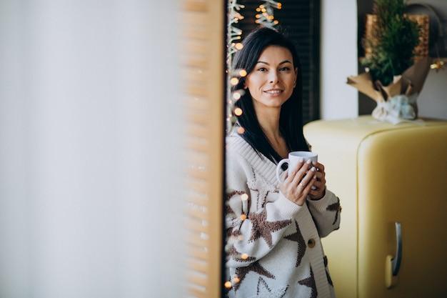 Joven bebiendo café junto a la ventana