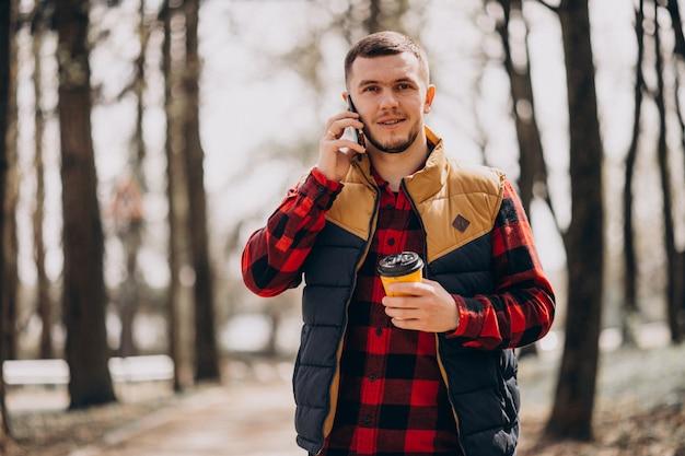 Joven bebiendo café en el parque y usando el teléfono