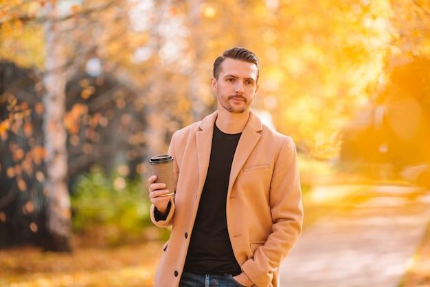Joven bebiendo café con teléfono en otoño parque al aire libre