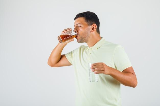 Joven bebiendo cola mientras sostiene el vaso de agua en la camiseta