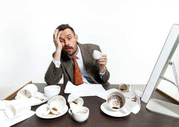 Joven bebiendo mucho café, pero no puede despertarse y trabajar de todos modos. sigue durmiendo en la oficina. concepto de problemas, negocios, problemas y estrés del oficinista.