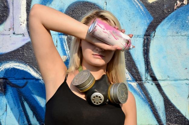 Joven y bella artista de graffitis sexy con máscara de gas en su cuello escondiendo sus ojos