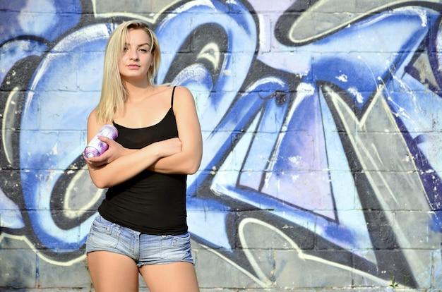 Una joven y bella artista de graffitis sexy con un spray de pintura.