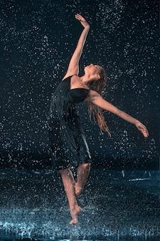 La joven y bella bailarina moderna bailando bajo gotas de agua