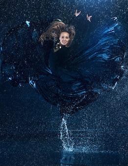 Joven y bella bailarina moderna bailando bajo gotas de agua