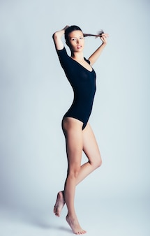 Joven y bella bailarina posando en studio