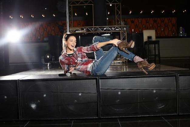 Joven y bella cantante pop estrella sonriente con micrófono sentado en la escena en el club