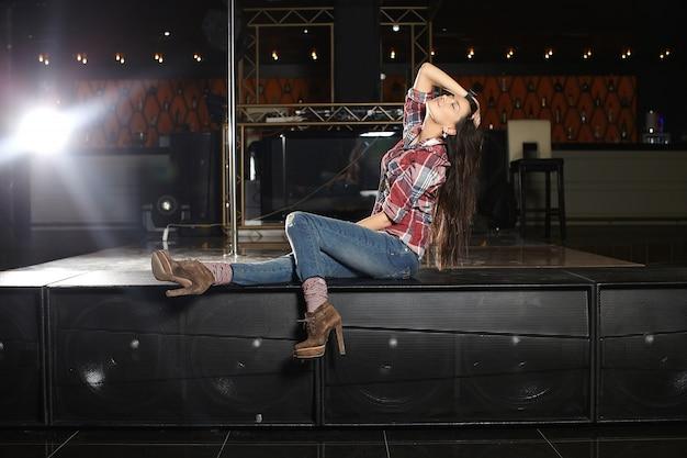 Joven y bella cantante de pop con micrófono sentado en la escena en el club