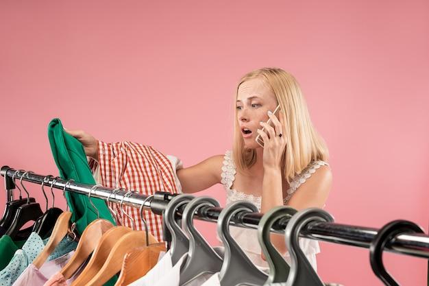 La joven y bella chica mirando vestidos y probándose mientras elige en la tienda