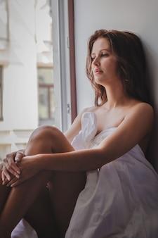 Una joven y bella chica morena en un hotel sentado en una manta en la ventana