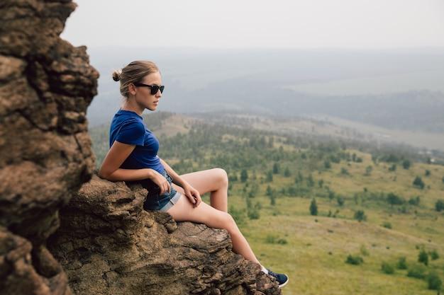 Joven y bella chica rubia turista se sienta en una repisa rocosa de una roca y mira lejos en la distancia en la madrugada brumosa.