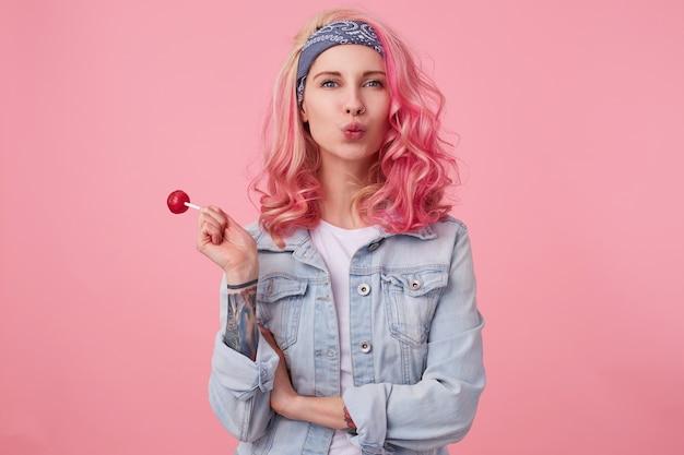 Joven y bella dama de pelo rosa feliz en denim shir, sosteniendo una piruleta, mira, sedns kiss, stands.