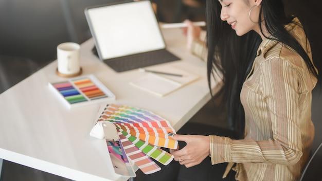 Joven y bella diseñadora asiática que trabaja en su proyecto mientras usa una tableta digital