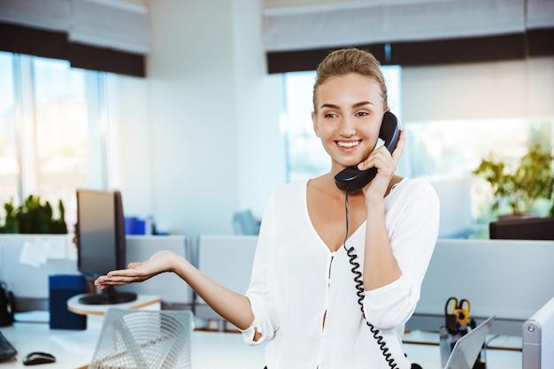 Joven y bella empresaria exitosa sonriendo, hablando por teléfono, sobre la oficina