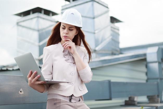 Joven y bella empresaria en traje beige, pantalón marrón y casco sentado en el techo y sostiene la computadora portátil