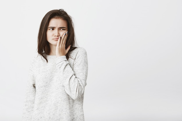 Joven y bella modelo femenino con cabello castaño, sosteniendo la palma en la mejilla, expresando infelicidad, cansancio y frustración