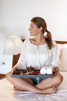 Una joven y bella morena en posición de loto se sienta en una cama con una bandeja en sus manos con un café y galletas, decoraciones, una tetera china. hermoso tiempo de desayuno en la cama