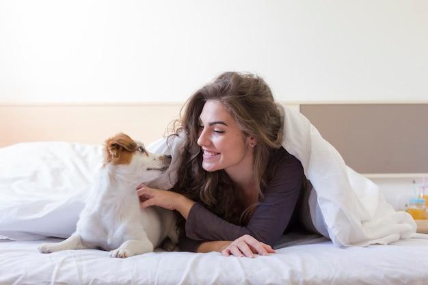Joven y bella mujer acostada en la cama bajo la cubierta blanca con su pequeño perro lindo. hogar, interior y estilo de vida.