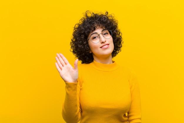 Joven y bella mujer afro sonriendo feliz y alegremente, saludando con la mano, dándole la bienvenida y saludando, o diciéndole adiós