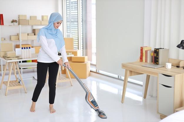 Joven y bella mujer ama de casa musulmana asiática activa de limpieza con piso de limpieza al vacío