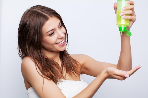 Joven y bella mujer aplica acondicionador en el cabello dañado para restaurar y cuidar el cabello
