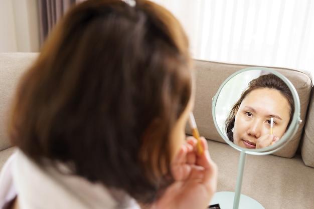 Joven y bella mujer asiática aplicando maquillaje frente a un espejo en casa. pintura de cosméticos