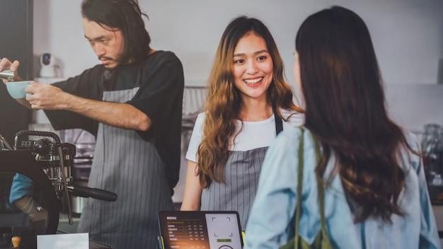 Joven y bella mujer asiática barista llevar delantal con taza de café caliente servido al cliente en barra de bar en la cafetería con cara de sonrisa