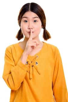 Joven y bella mujer asiática con el dedo en los labios
