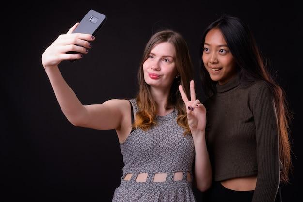 Joven y bella mujer asiática y joven y bella mujer escandinava juntos